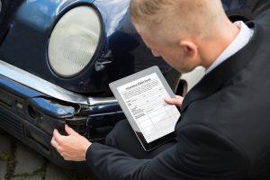 Man Holding Digital Tablet Examining Damaged Car