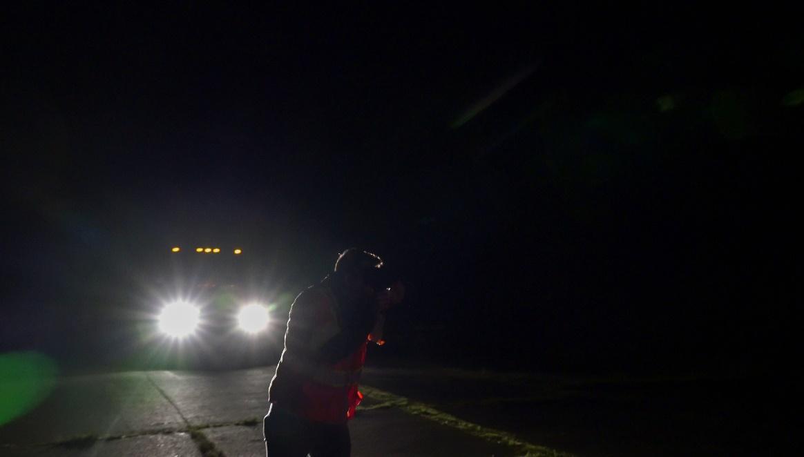 car headlights shining on road crew worker at night